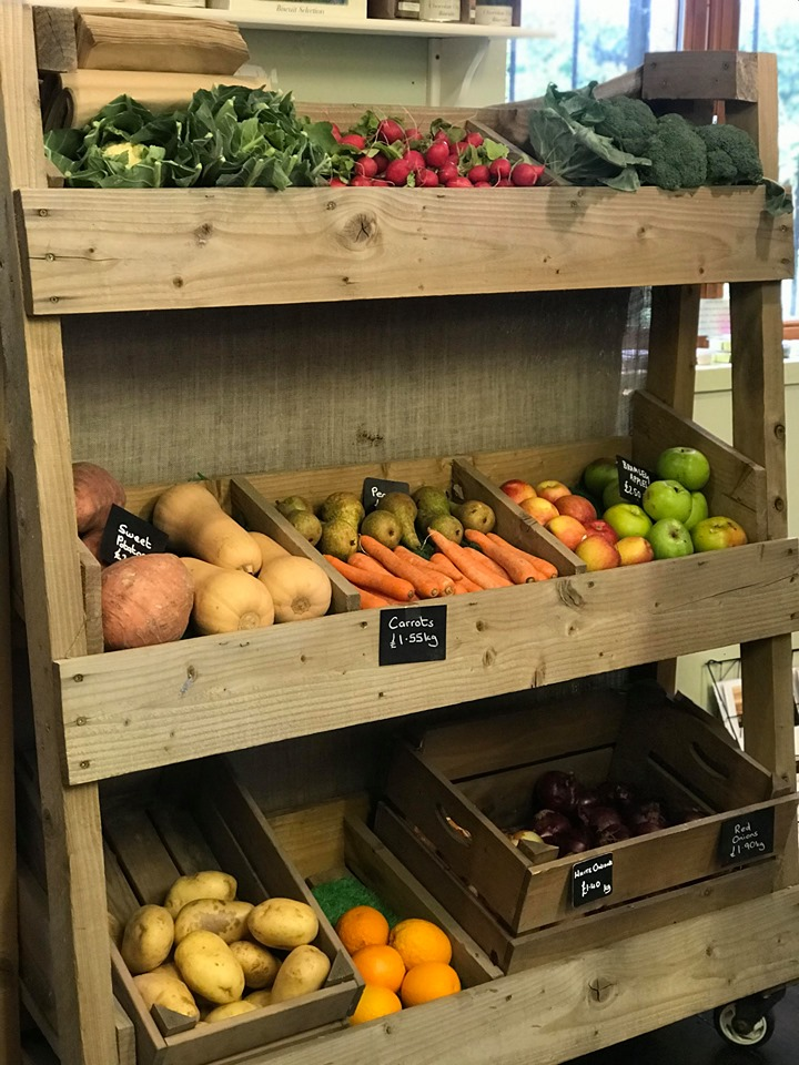 A photo of a large wooden display unit containing a range of vegetables, carrots, butternut squash, broccoli, cauliflower, radishes, apples etc.