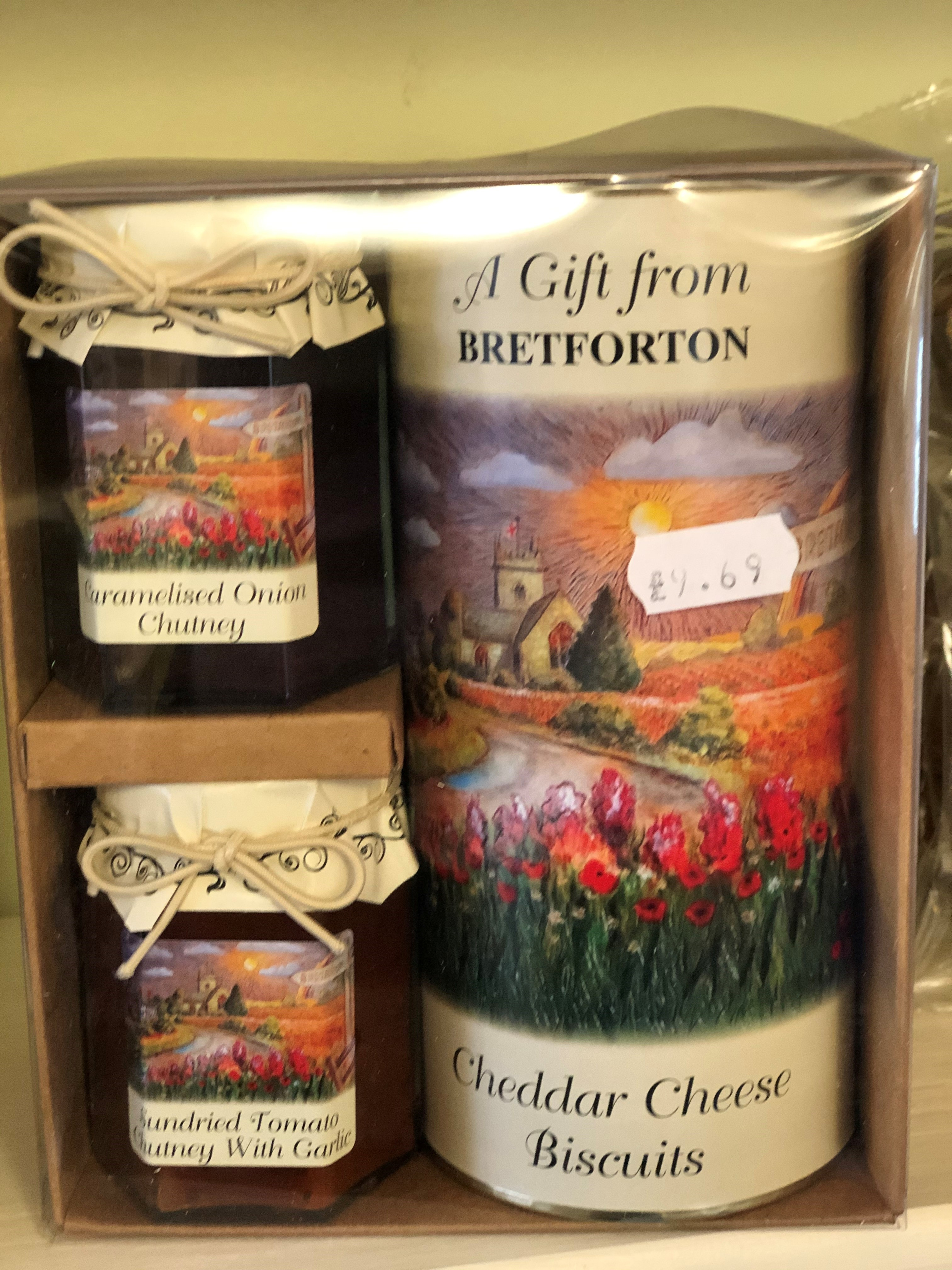 "A photo of a gift pack of ""Gifts from Bretforton"", showing jars of caramelised onion chutney, sundried tomato chutney and a tube of cheddar cheese biscuits. Gifts have a reproduction of the oil painting of Bretforton that is displayed in the Shop on them"